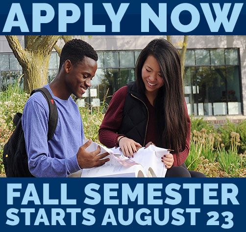 It's not to early to apply now for Fall Semester with picture of students sitting outside a building flipping through a book.