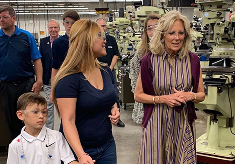 Jill Biden walking in an area with Tool and Die Machines talking with a mother who is holding her young child by the hand.