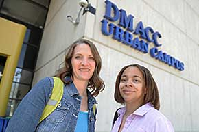 Two students standing in front of the urban campus sign