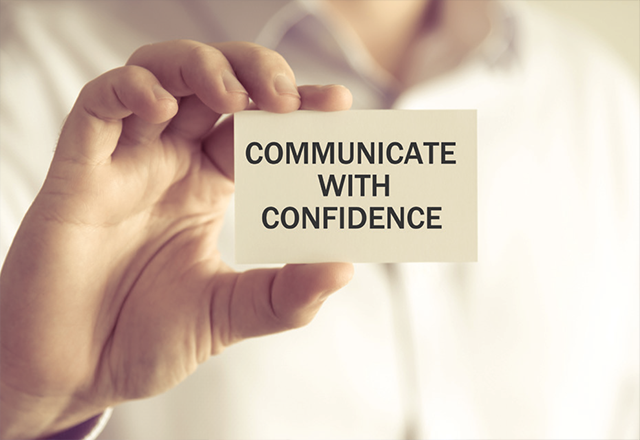 hand holding card that says Communicate with Confidence