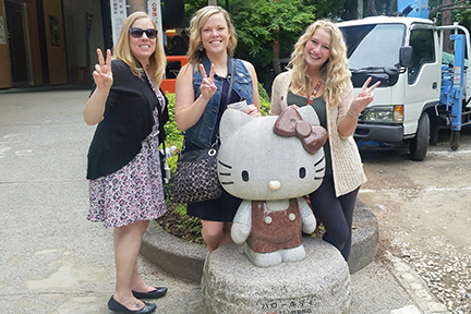 Dental Hygiene student pose behind Hello Kitty statue in Japan