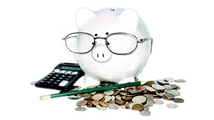 Piggy bank with glasses on surrounded by change, a pencil and a calculator